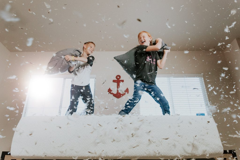 Boys having a pillow fight on the bed