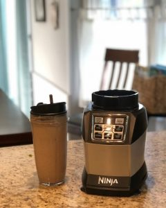 Ninja Blender and Blender cup filled with blended protein smoothie.