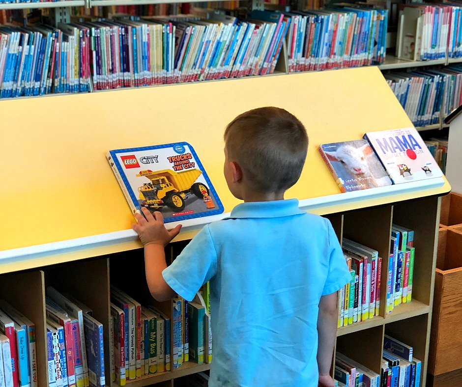 A young boy picking out a book at the library