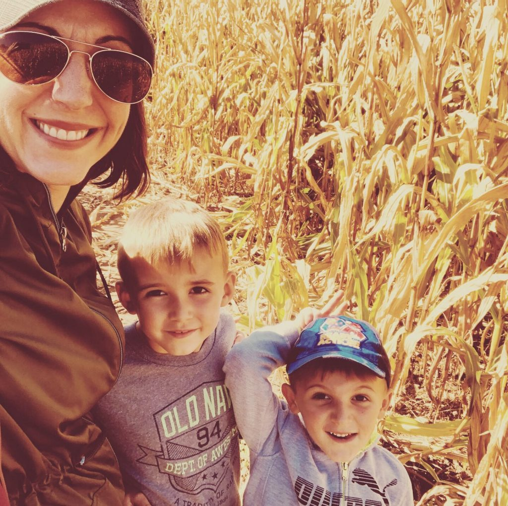 Mom and two boys in a corn maze in the fall