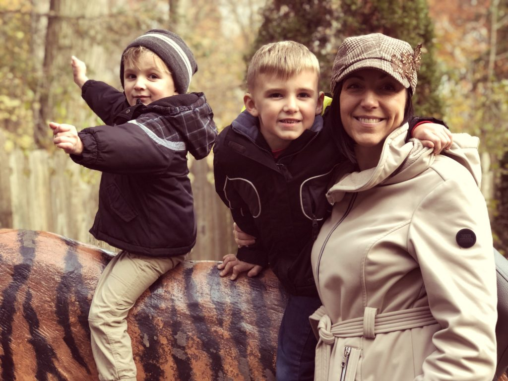 mother with two boys on a tiger at the zoo in the fall
