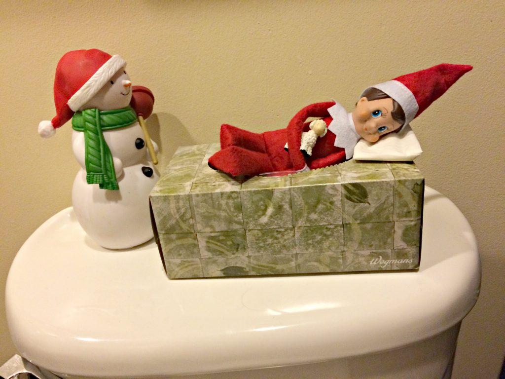 Elf on the shelf sleeping in a kleenex box