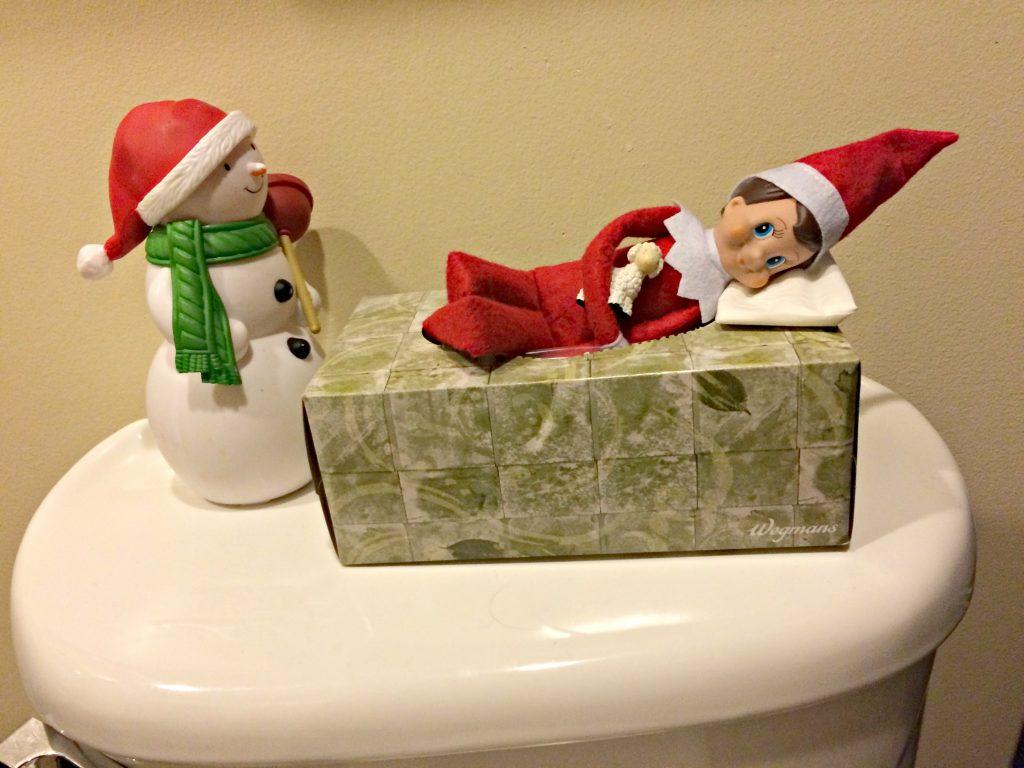 Elf on the shelf sleeping in a kleenex box