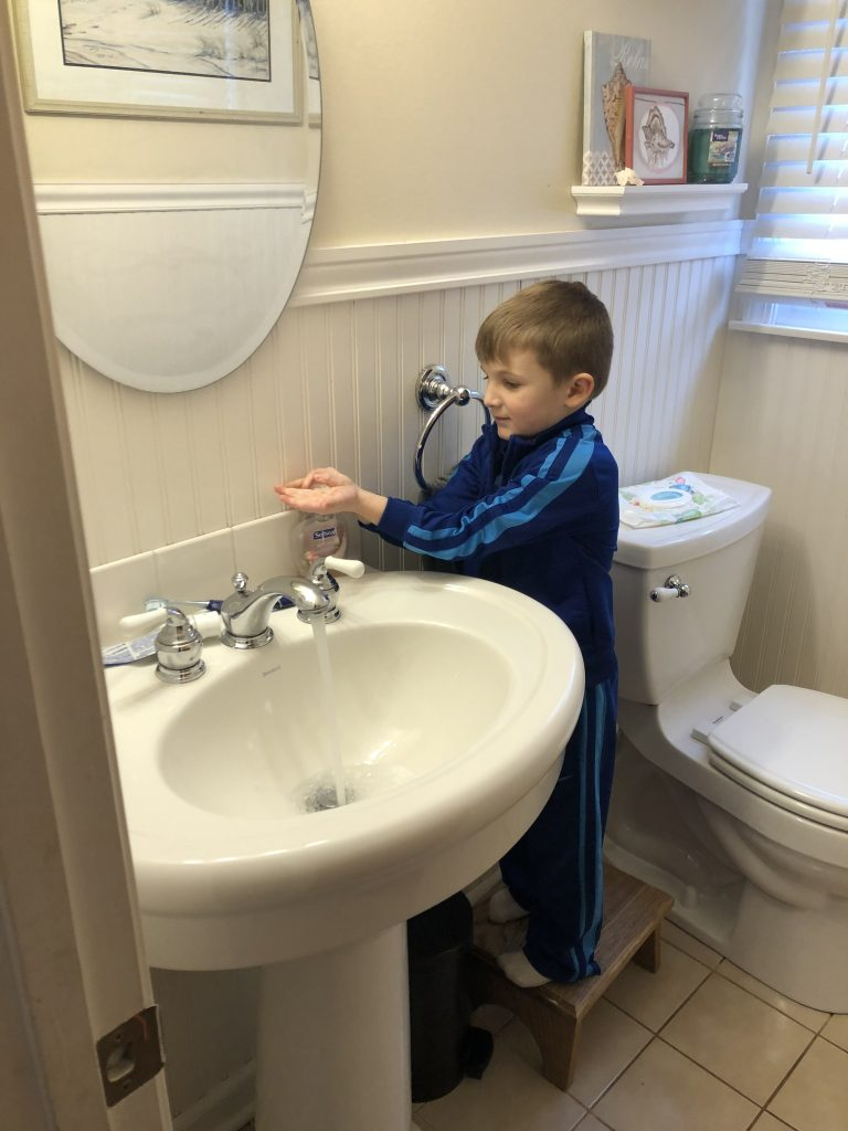 Boy washing his hands as part of the afternoon routine