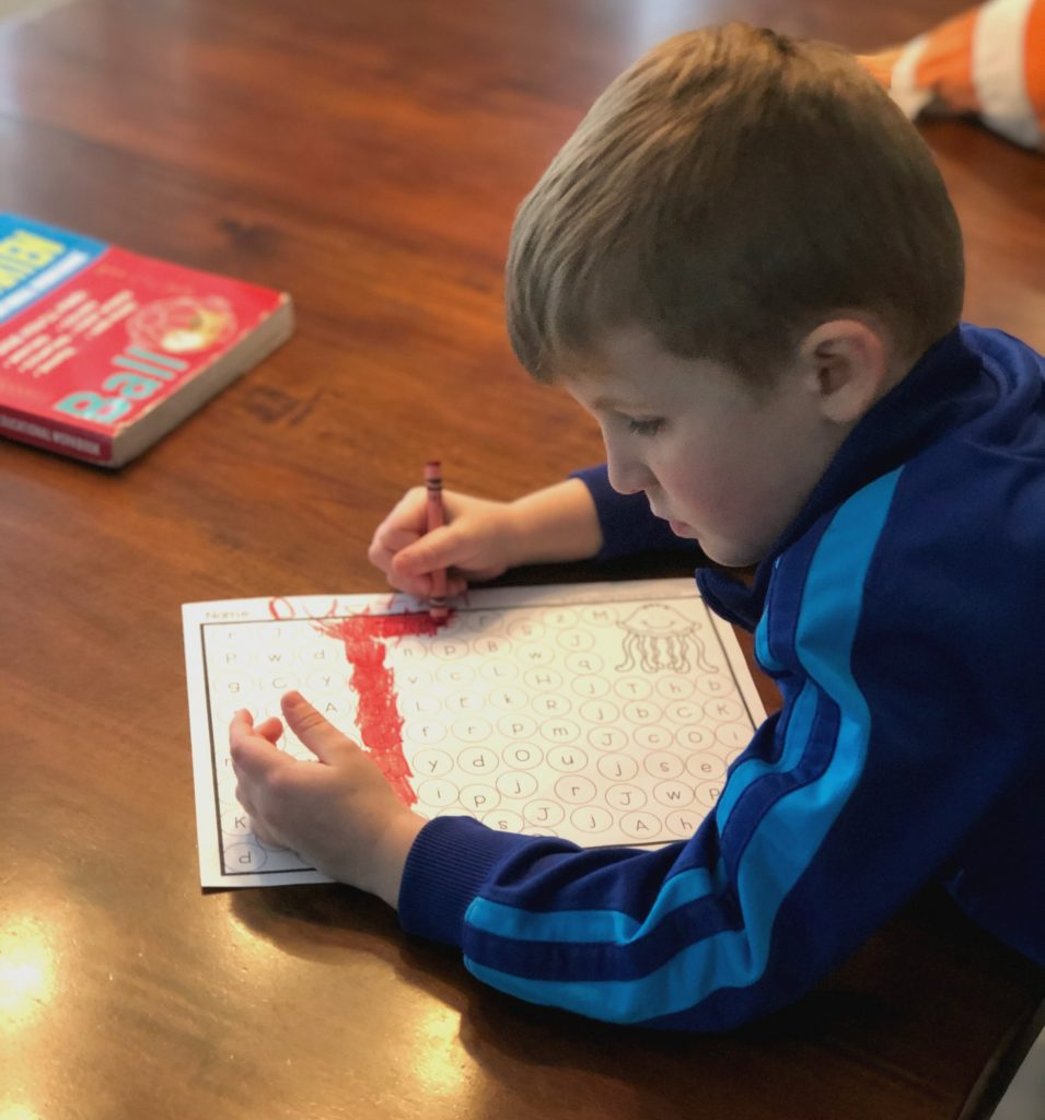 Boy doing educational worksheet as part of the afternoon routine
