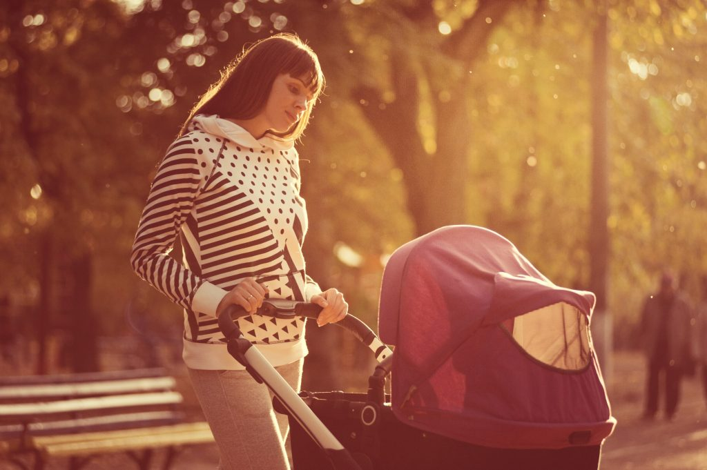 Mom walking baby in a stroller. Mom looks overwhelmed.