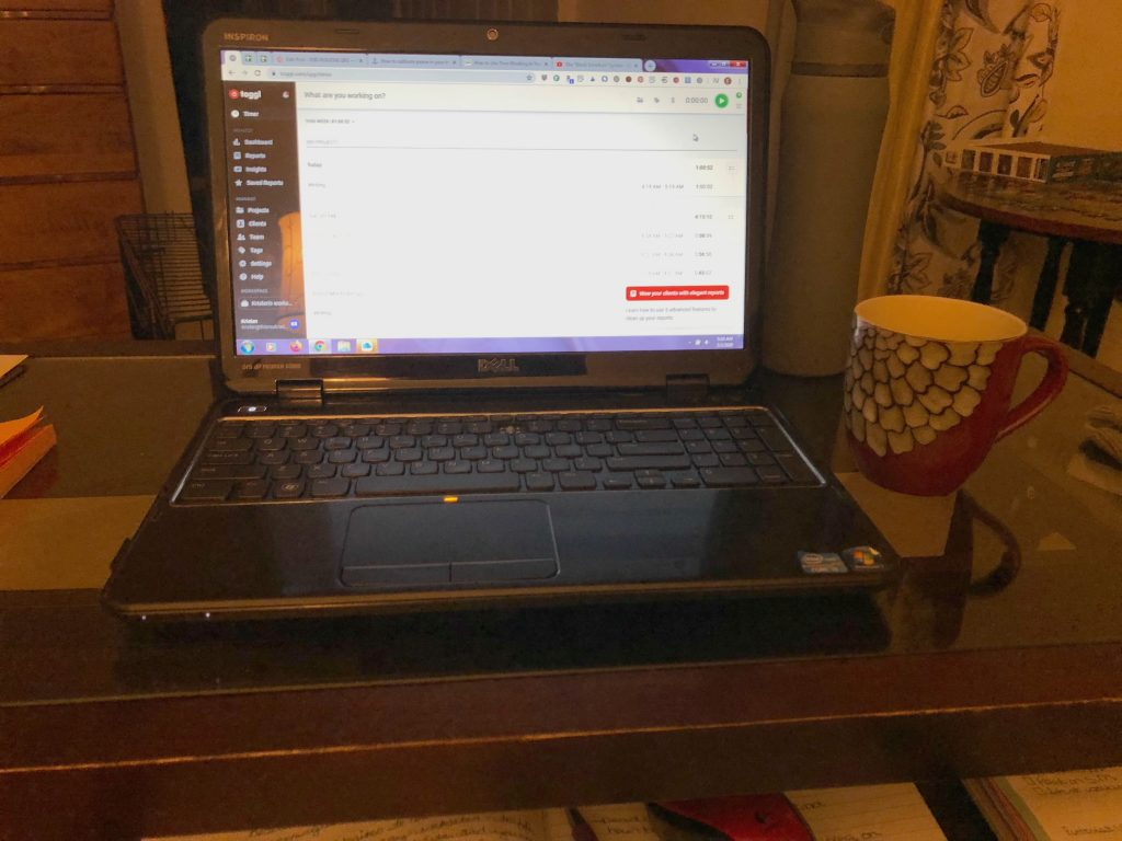 A computer and coffee cup on a desk used for writing during the morning routine.
