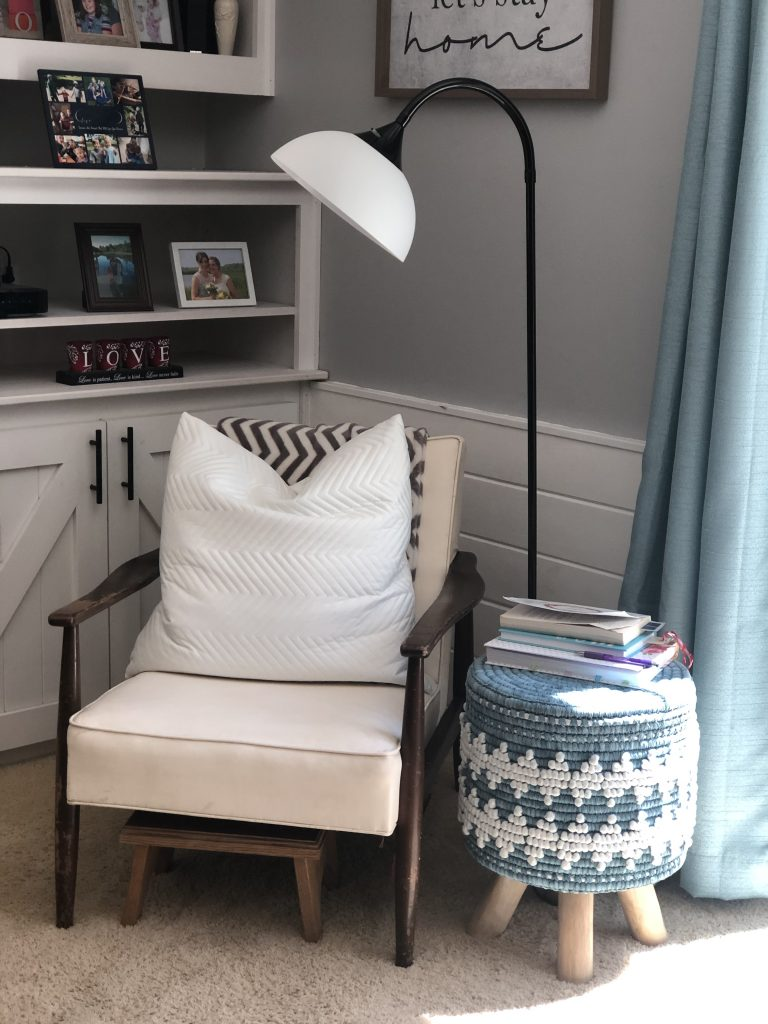 A chair with a pillow and a lamp and a stool that has books on top to read and write in during the morning routine.